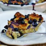 A slice of blueberry breakfast bake on a white plate with a yellow napkin.