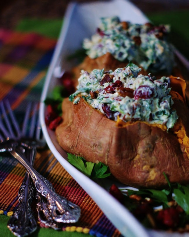 Upclose of stuffed sweet potatoes with cranberries, bacon, spinach, walnuts and goat cheese