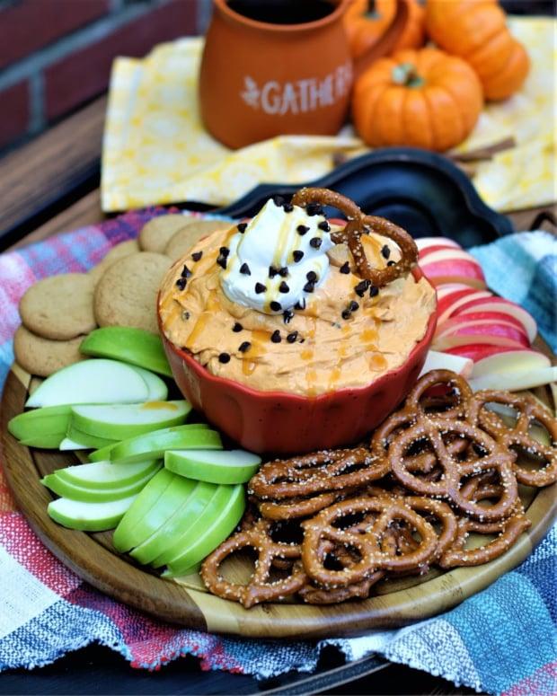Pumpkin butterscotch dip on a platter of pretzels, gingersnaps, green and red apples.
