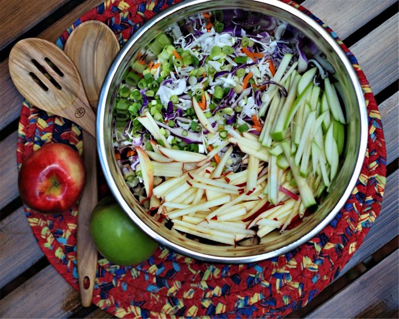 the ingredients for apple coleslaw in a mixing bowl.
