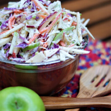 Apple coleslaw with red and green apples, purple and green cabbage and carrots.