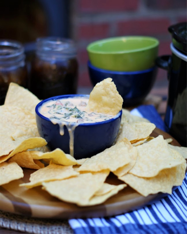 Queso dip with collard greens and sausage in a blue dip bowl surrounded by corn chips.