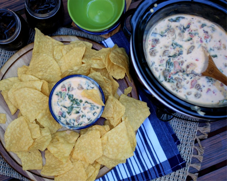 Queso dip with collard greens and sausage served with corn chips and made in a crock pot.
