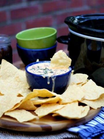 Queso dip with collard greens and spicy sausage served with corn chips and cooked with a crock pot.