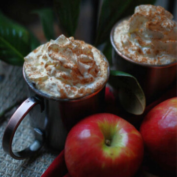 Two mugs of Caramel Apple Cider piled high with cinnamon whipped cream.