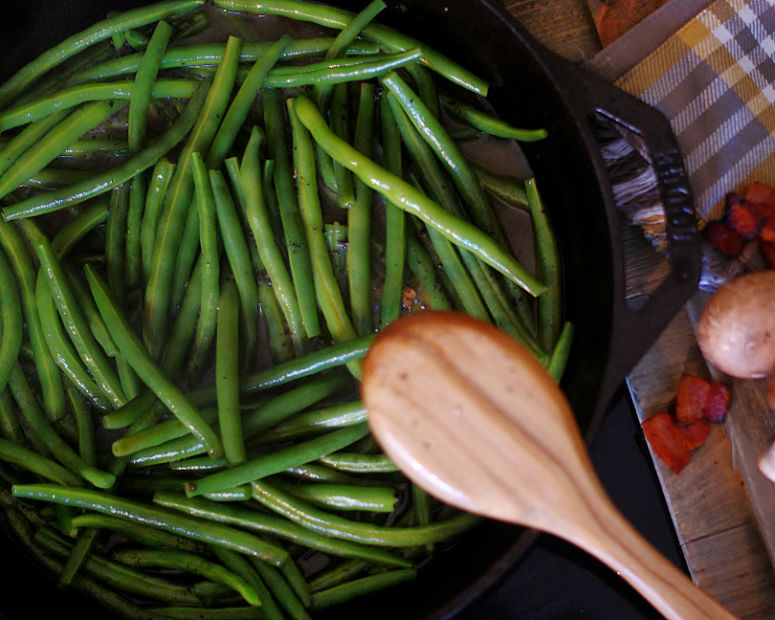 Green beans simmering in a skillet.