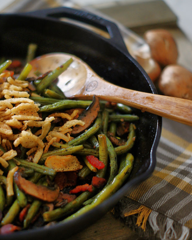 Sauteed green beans with bacon and mushrooms and topped with fried onion strips.