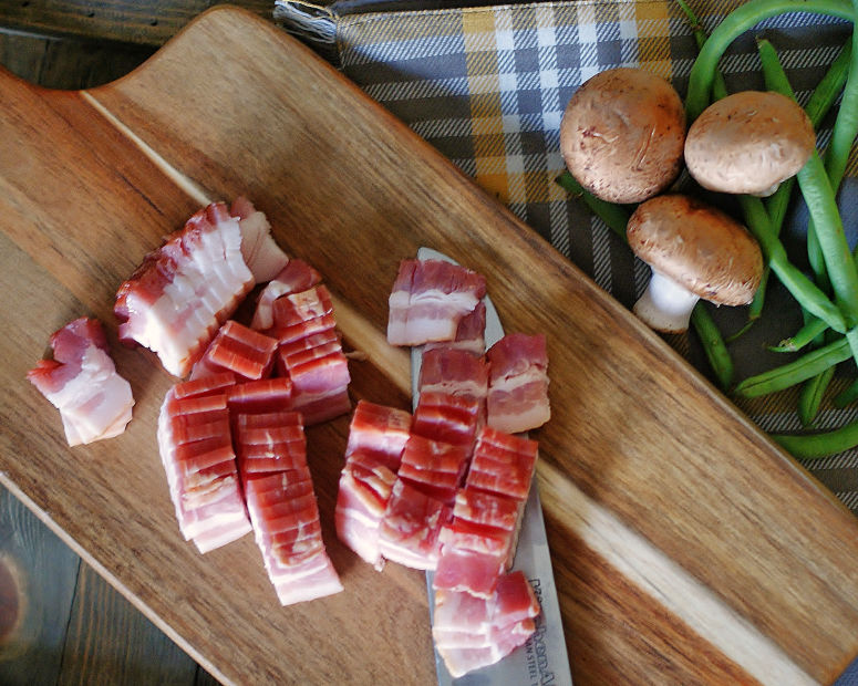 Bacon chopped on a cutting board to be cooked with the sauteed gree beans.