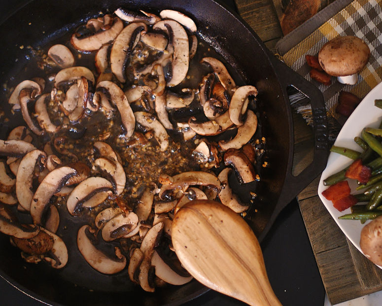 Mushrooms in a skillet being prepped for the sauteed greend bean dish.