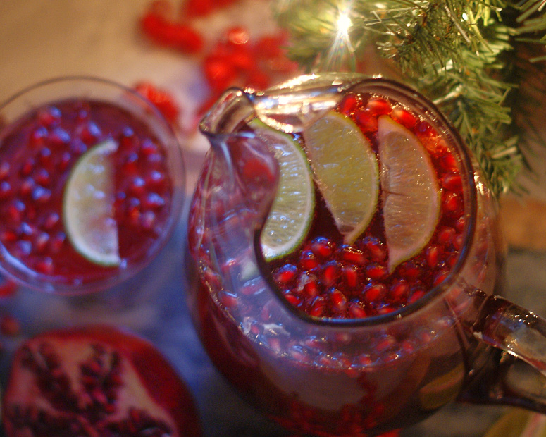 An aerial view of Pomegranate punch garnished with arils and lime slices in a pitcher.
