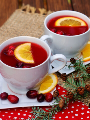 2 cups of cranberry red hot cider with orange slices and fresh cranberries.