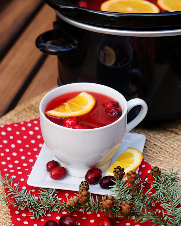 A cup of red hot cranberry cider with a crock pot in the background.