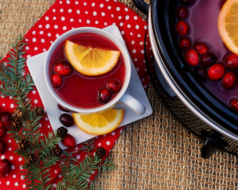 A cup of red hot cranberry cider and a crock pot.