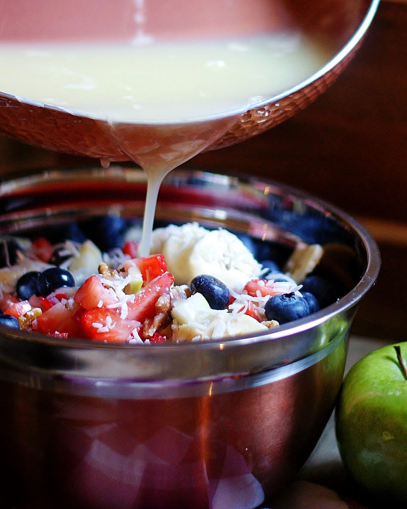 Old Fashioned Fruit Sauce being poured over a classic fruit salad.