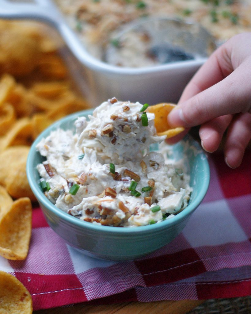 A bowl of Creamy Chicken Dip being dipped with a corn chip.