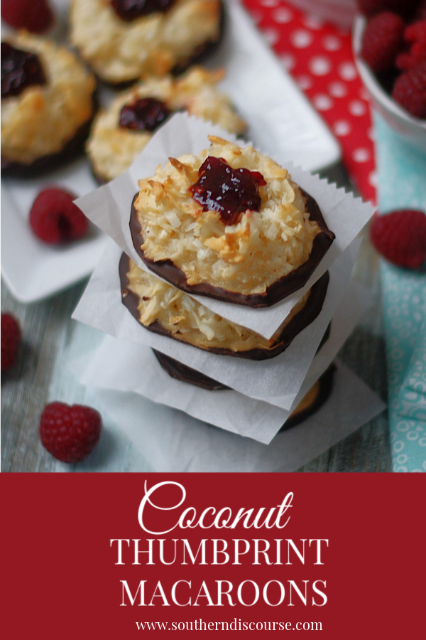 Sweet coconut and condensed milk are baked up then filled with raspberry jam and dipped in dark chocolate to create a wonderfully chewy decadent treat.  Coconut macaroons are such an easy, elegant dessert!  #coconut #macaroons #thumbprintcookie #noflour #southerndiscourse