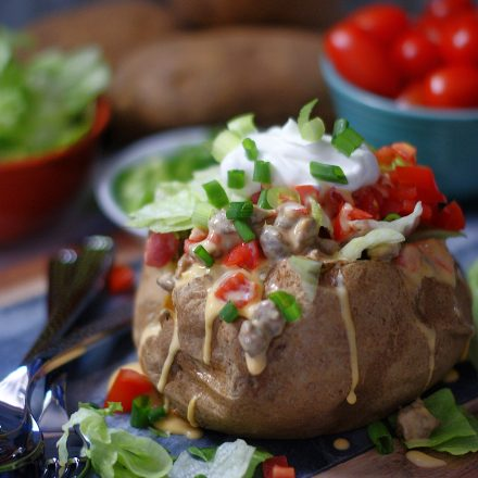 A baked potato stuffed with spicy sausage queso, lettuce, tomatoes and sour cream.