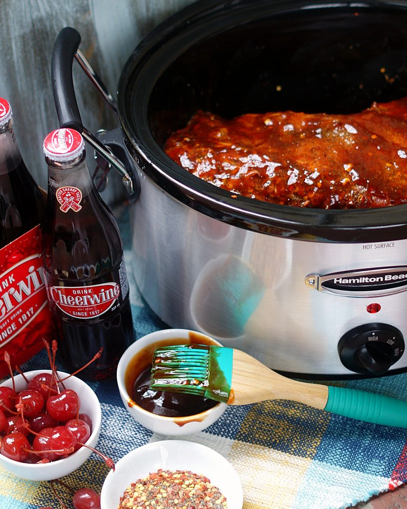 A pork tenderloin in the crock pot, rubbed with spices and coated with BBQ sauce.