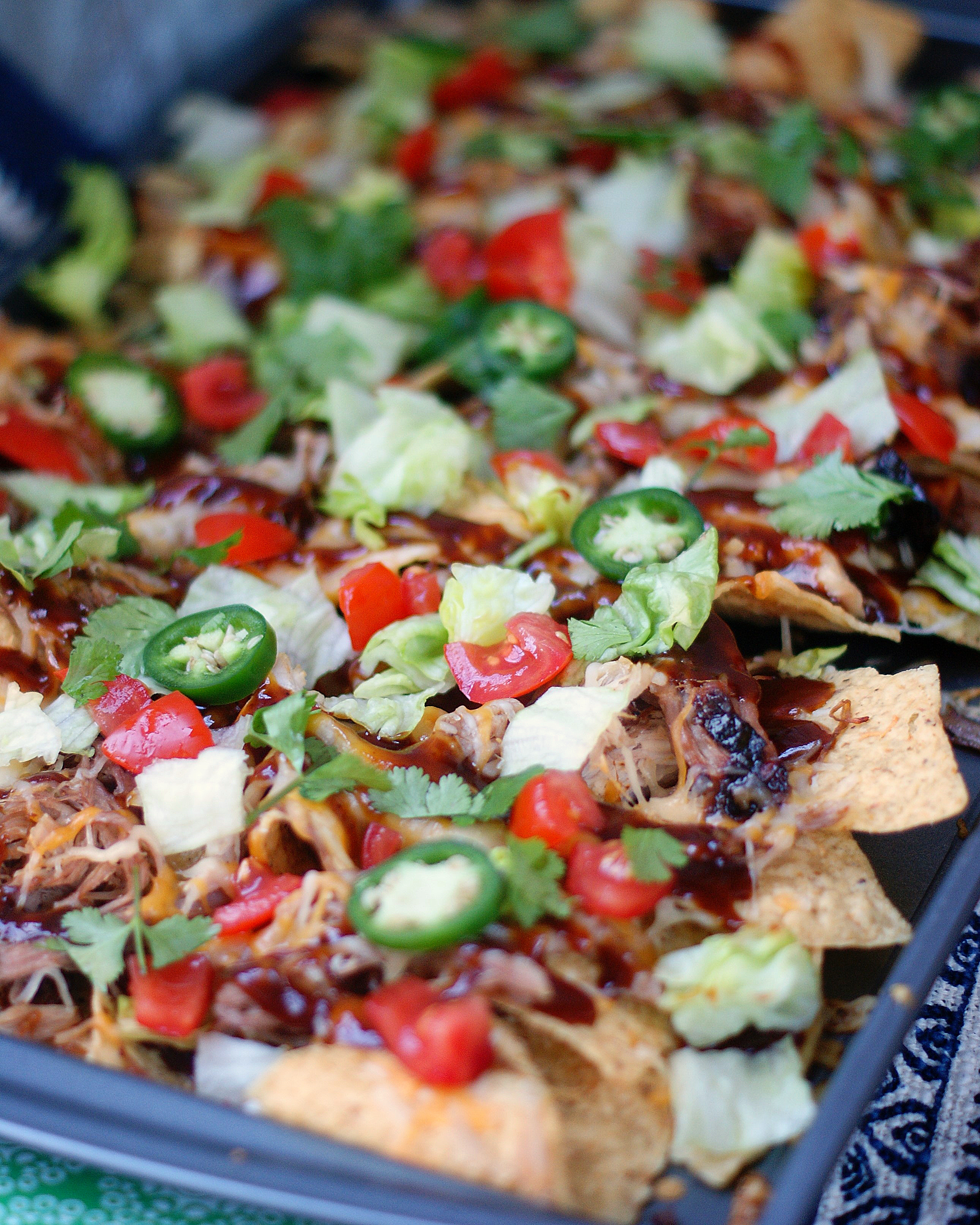 A full pan of sheet pan BBQ nachos with toppings