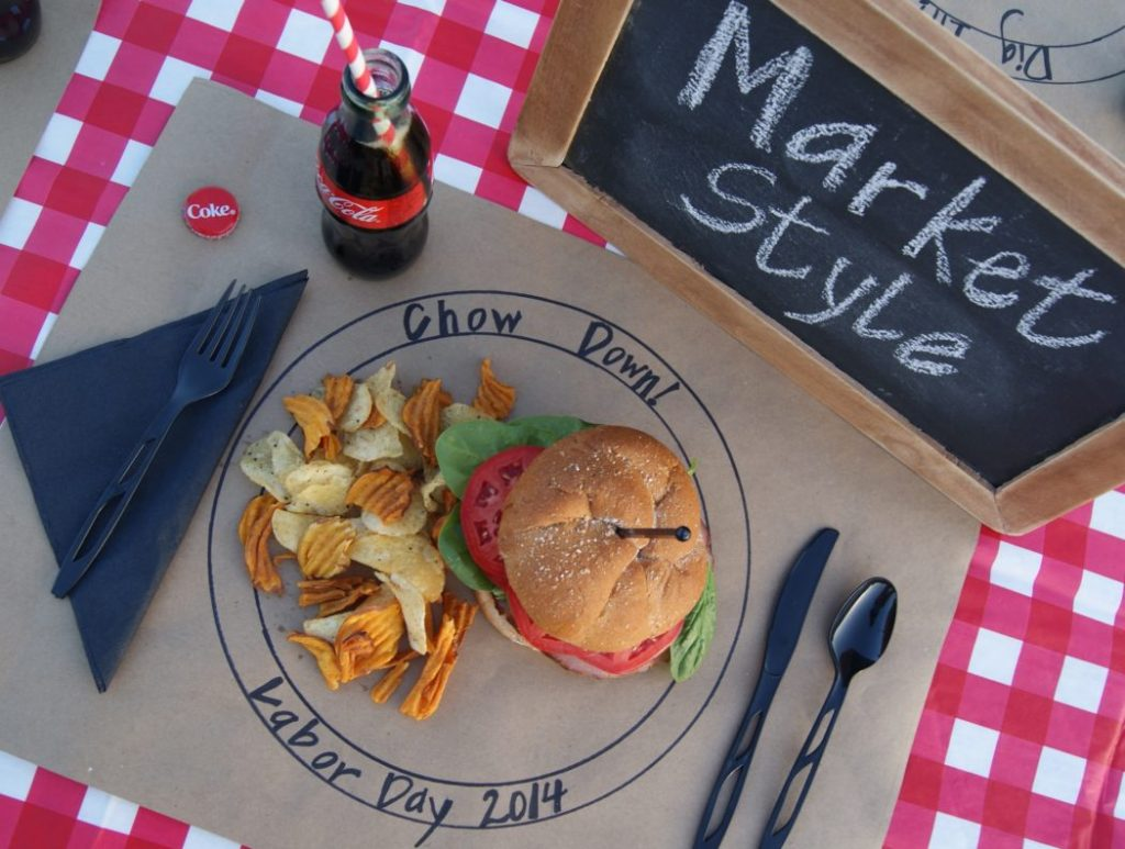 A place mat with a plate drawn on it and a sandwich served with chips.