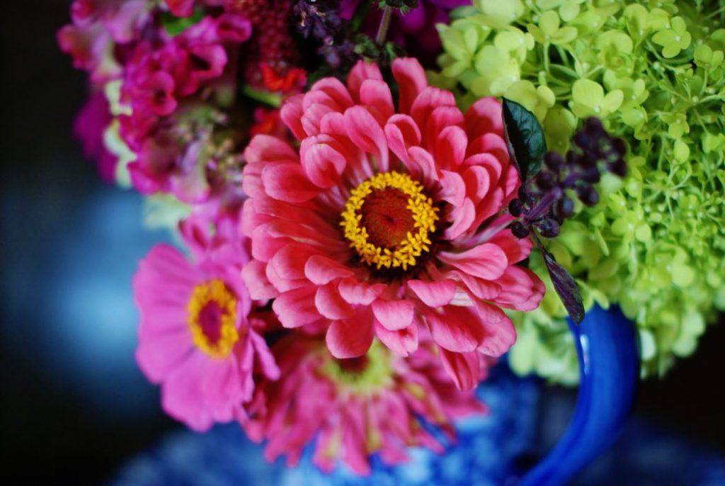 A bouquet of hot pink and green flowers in a blue vase