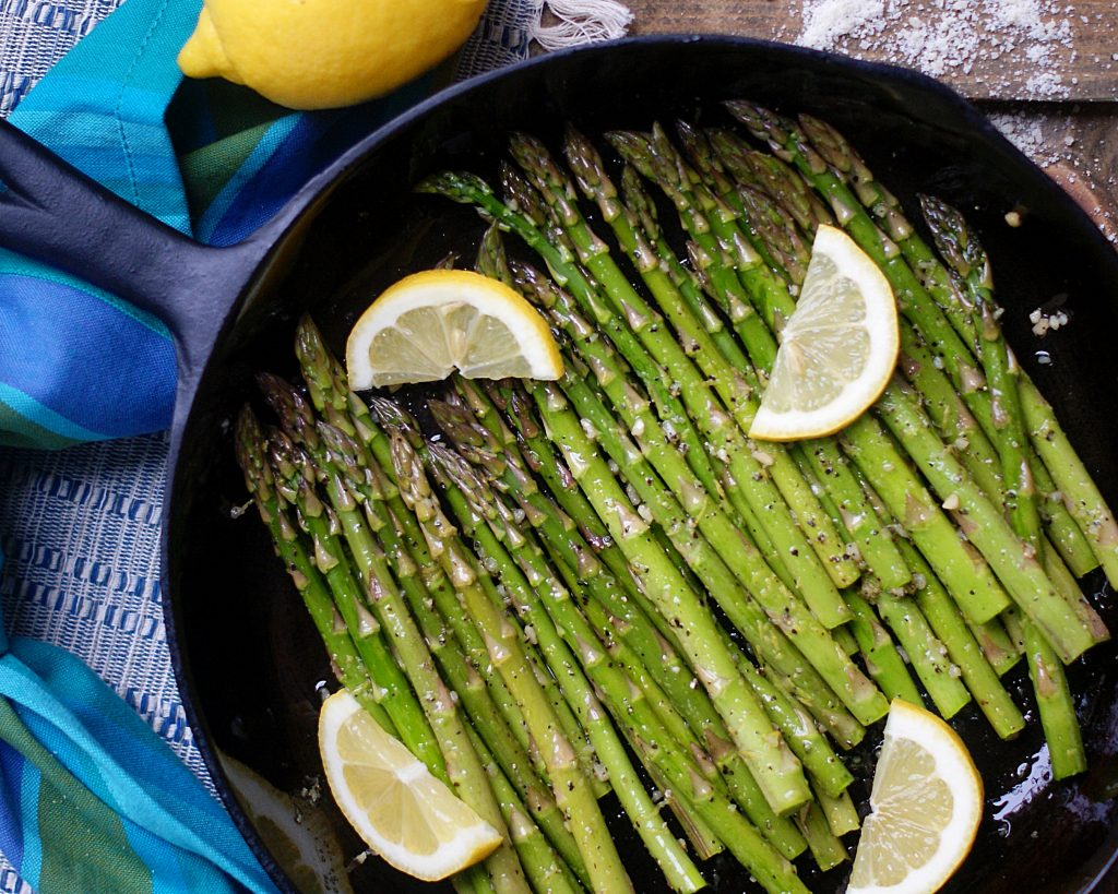Asparagus in a skillet ready to roast with lemon slices.