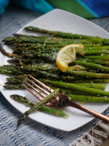 Roasted Lemon Asparagus on a white plate with a slice of lemon and parmesan cheese.