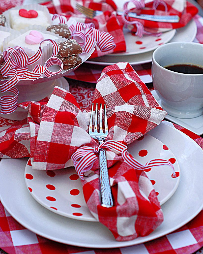 A red picnic checked napkin tied with a red and white ribbon on a red and white polka dot cake.