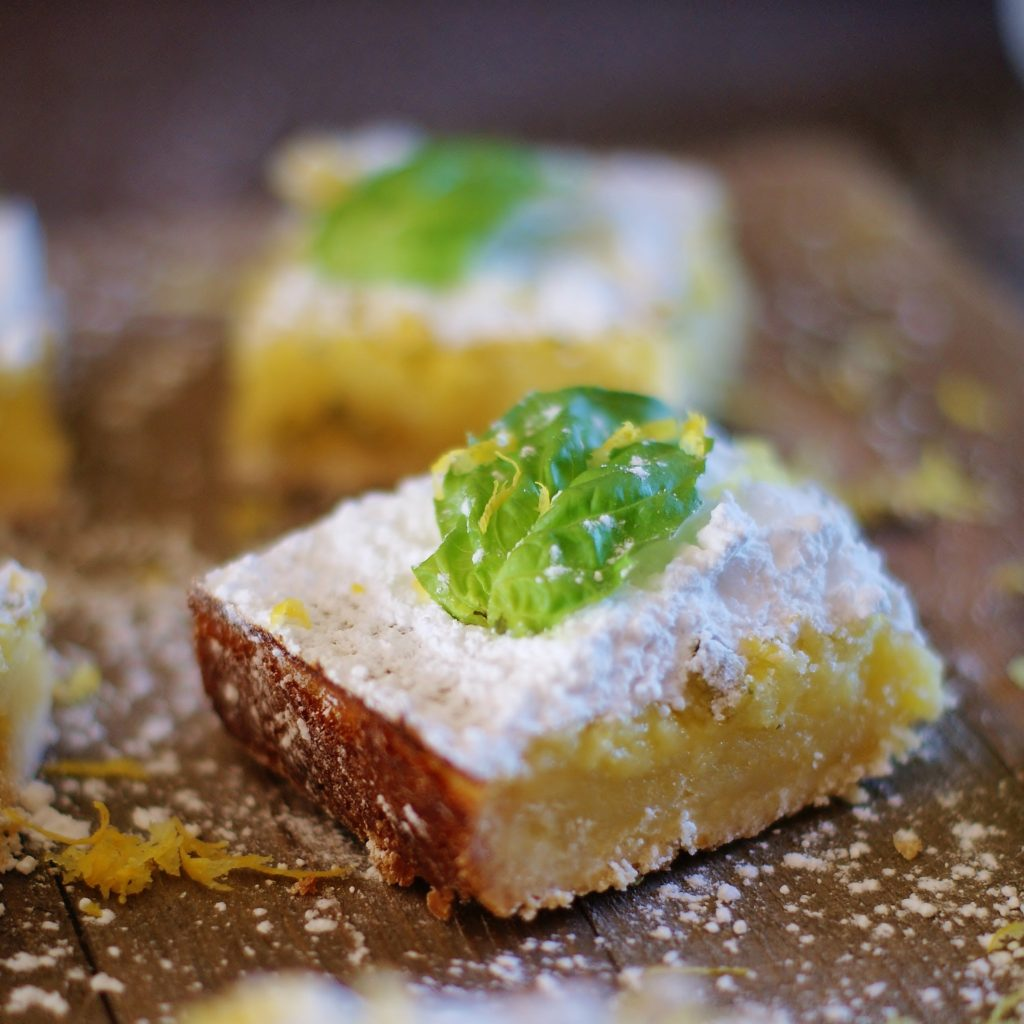 A classic lemon square topped with a basil leaf.