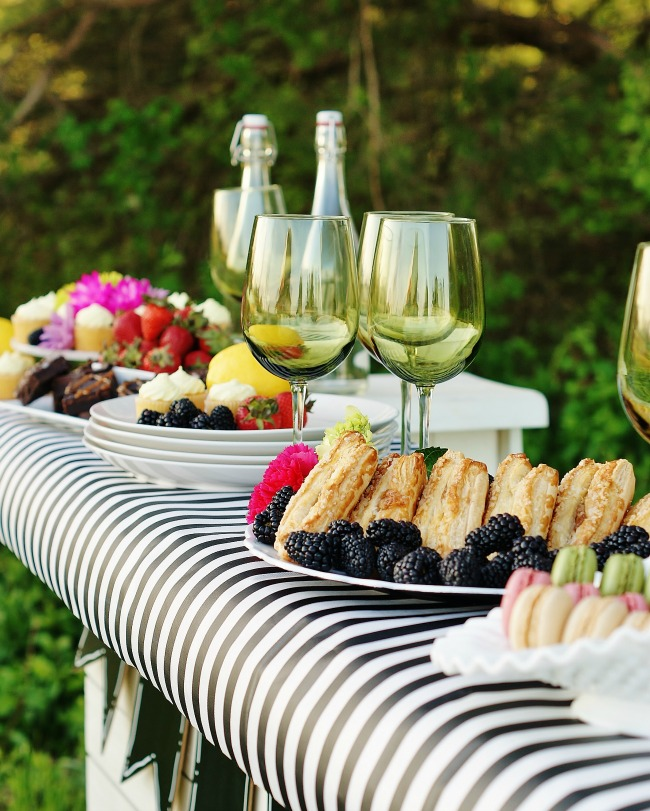 A spring dessert bar with desserts and green goblets.