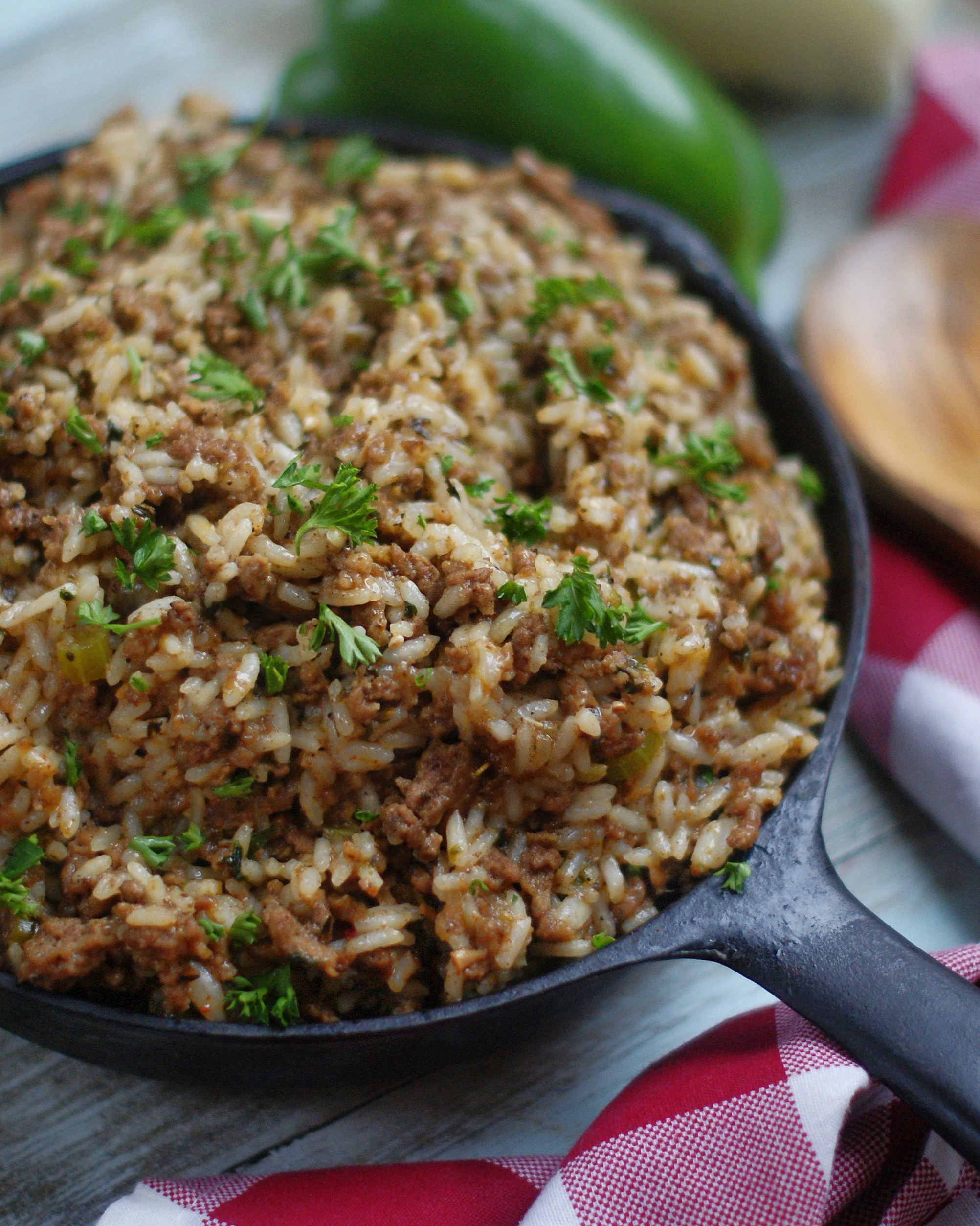 An upclose of Louisiana dirty rice in a cast iron skillet.