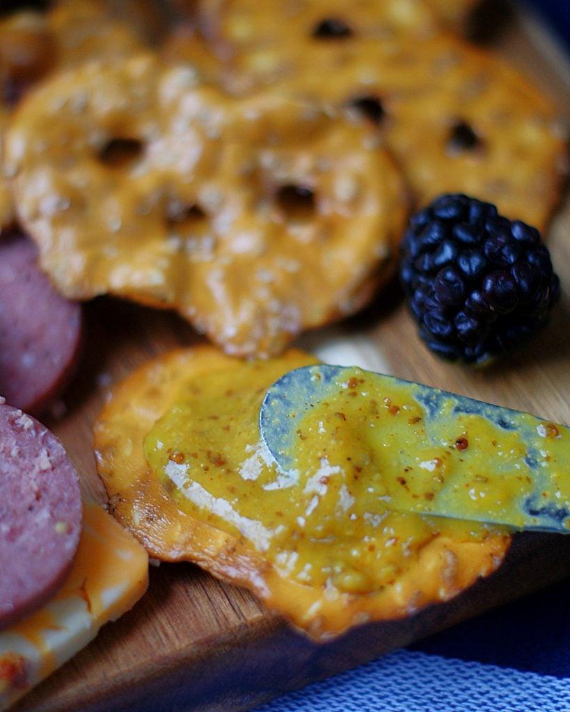 Honey & Pineapple Mustard spread on a cracker.
