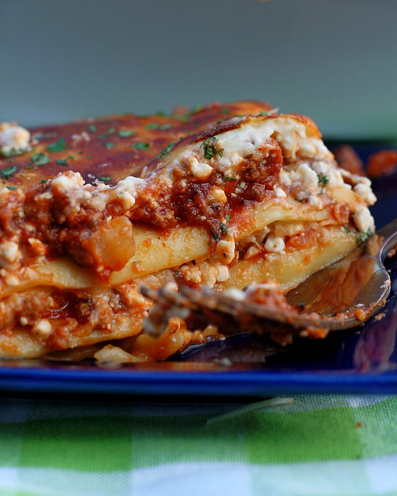 A slice of lasagna on a blue plate.