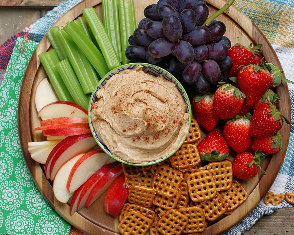 Finished peanut butter fruit dip in a bowl on a wooden platter with fruit.