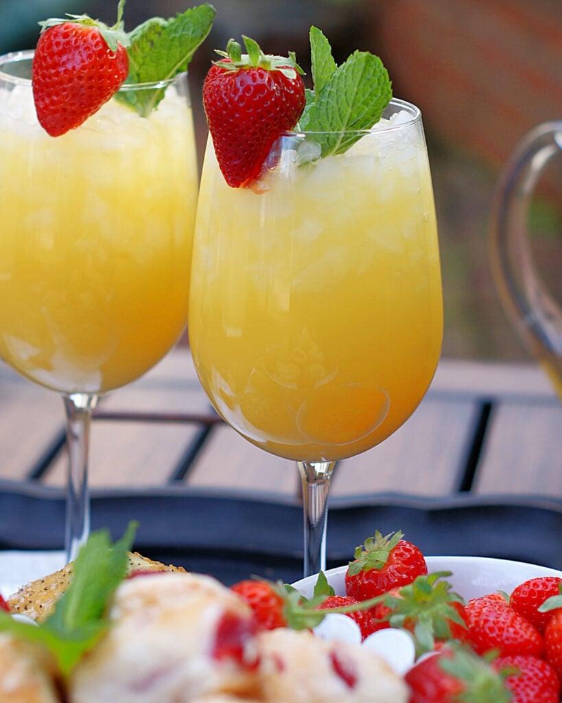 2 stemmed glasses filled with pineapple orange drink for brunch.
