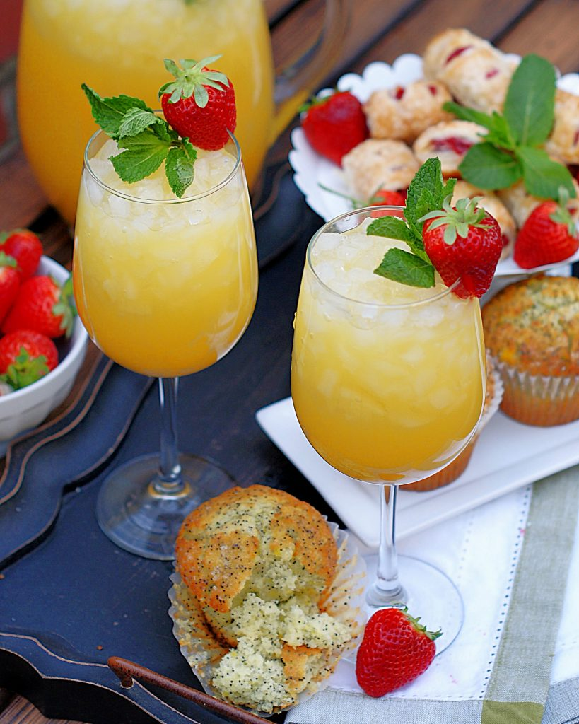 Garnished with mint and a strawberry, 2 glasses of pineapple orange fizzy are pictured with muffins and pastries.