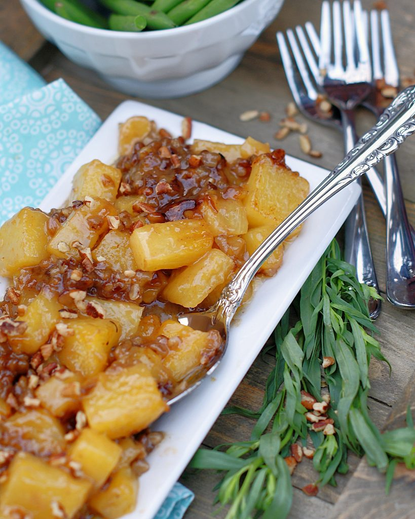 Roasted pineapple chunks in a brown sugar sauce with pecans.