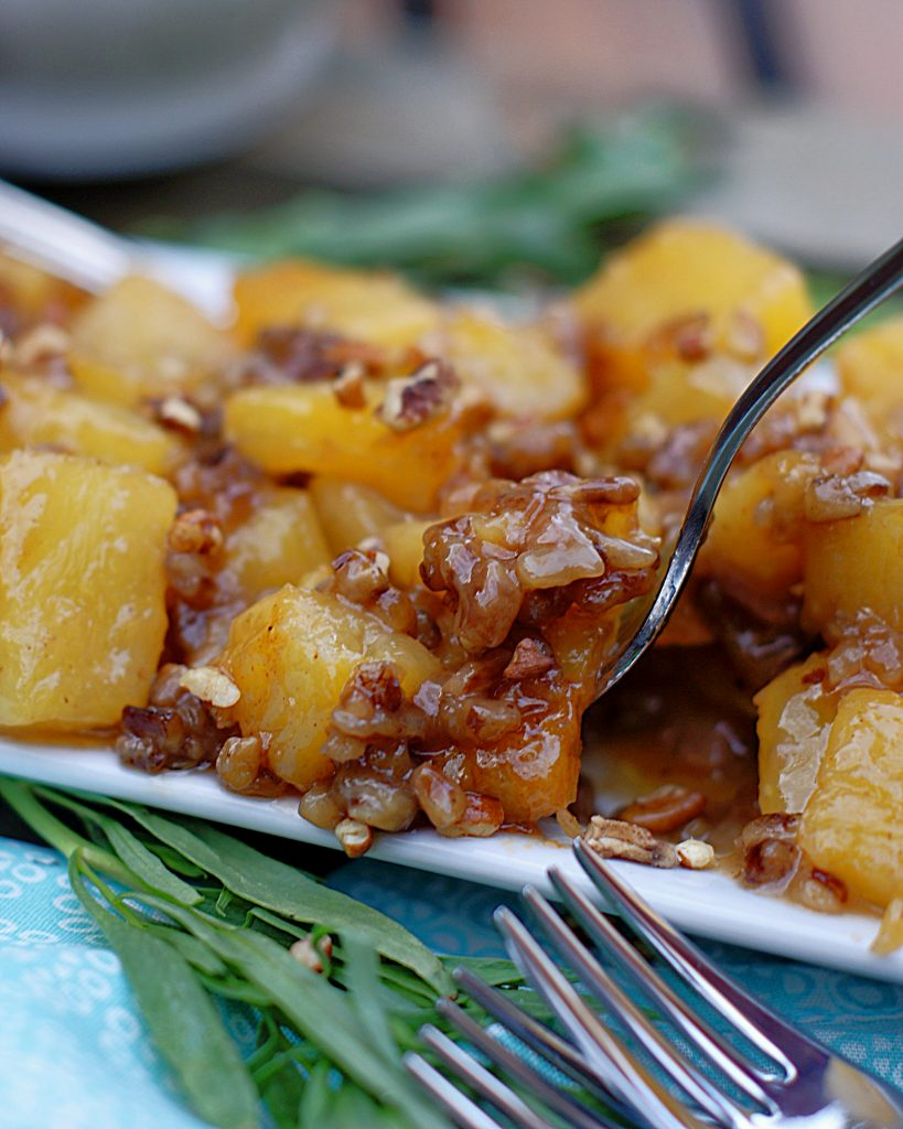 A fork full of roasted pineapples with brown sugar sauce and pecans.