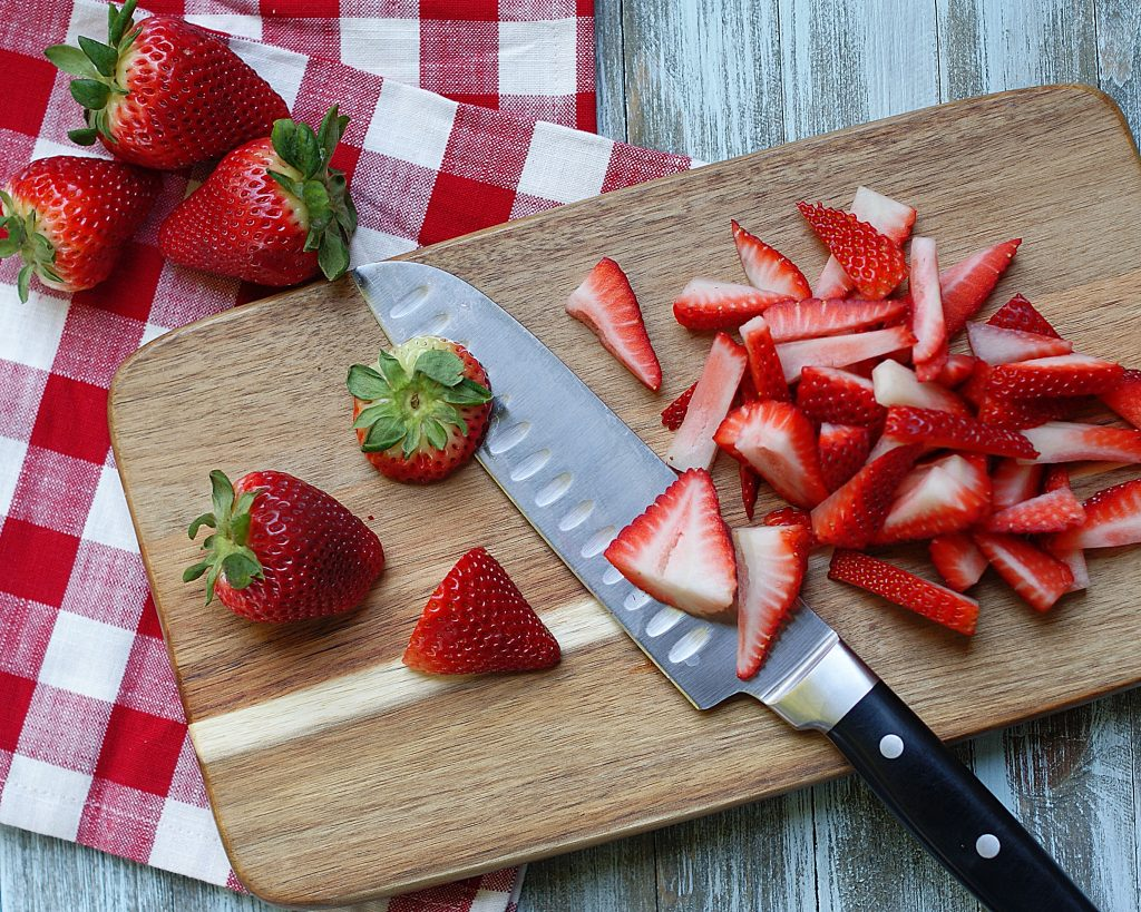 Sliced strawberries on a cutting board.