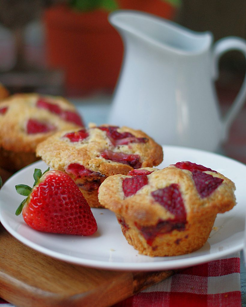 2 large farm style strawberry buttermilk muffins on a white plate with a white milk pitcher in the background.