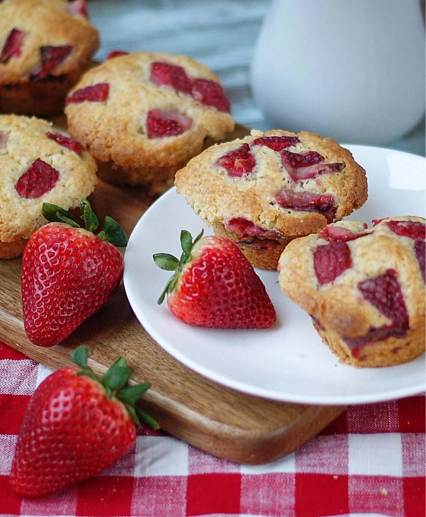 Strawberry muffins and strawberries piled on a wooden serving board.
