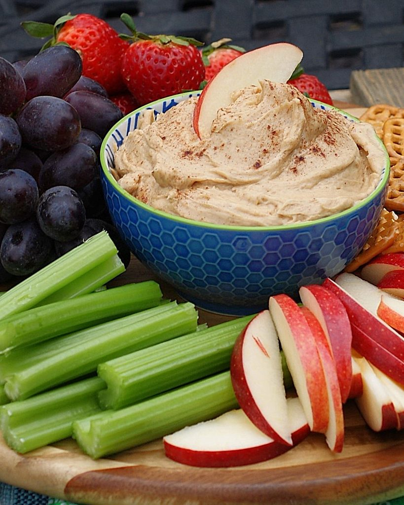An apple slice in peanut butter fruit dip.