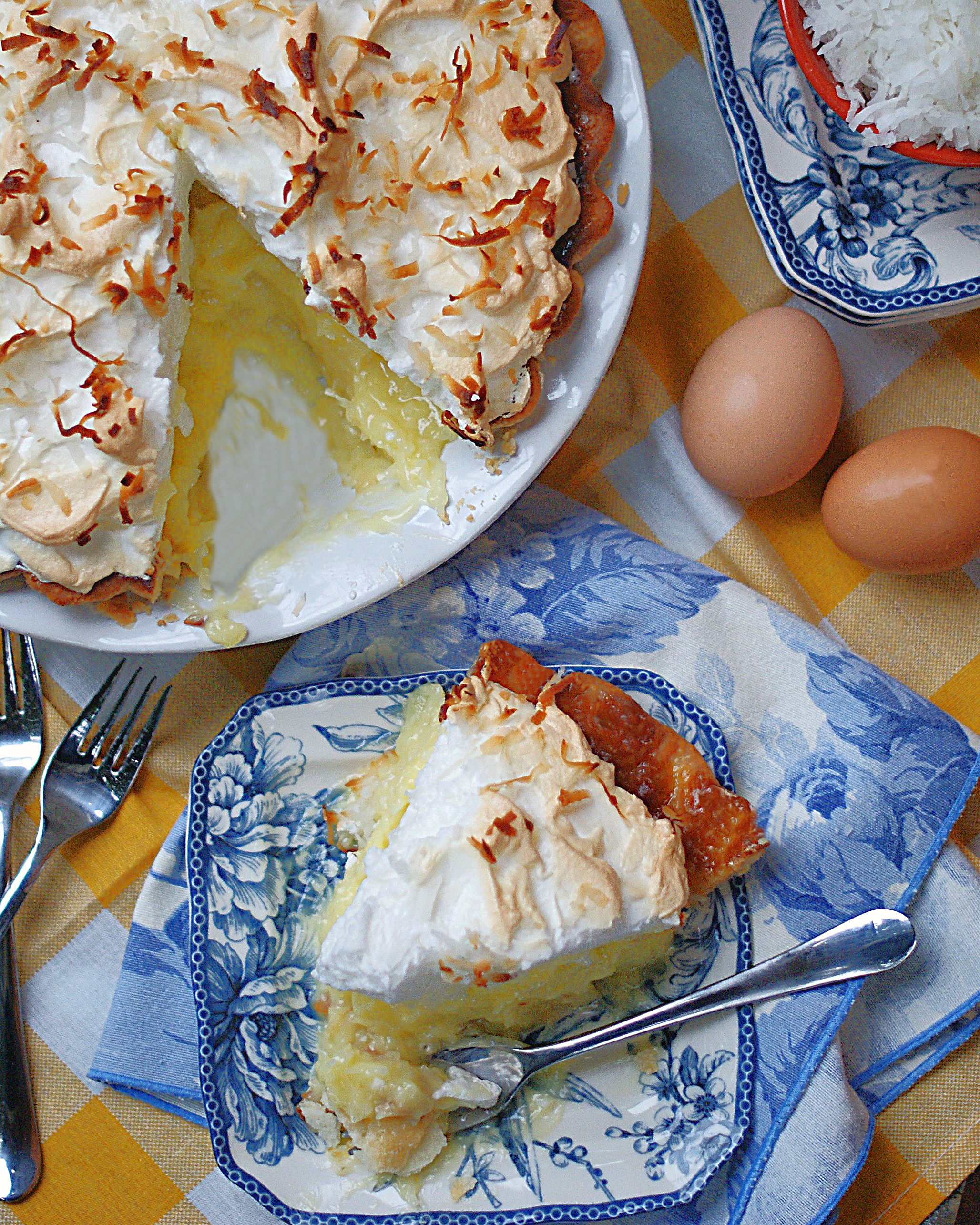 An overhead view of an old fashioned coconut pie with a meringue sliced.