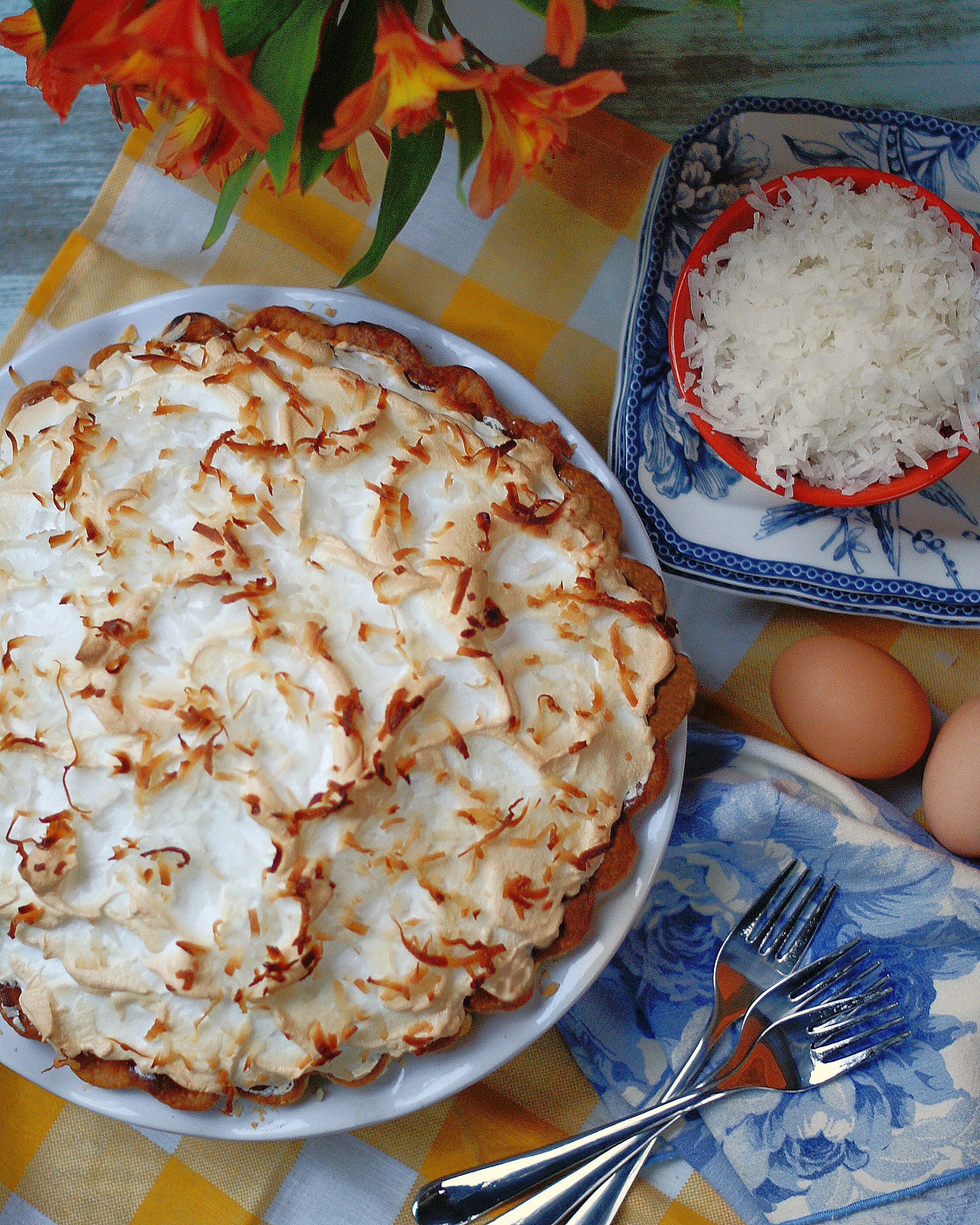 An aerial view of an old fashioned coconut cream pie with meringue complimented by blue and yellow napkins and 3 dessert forks.