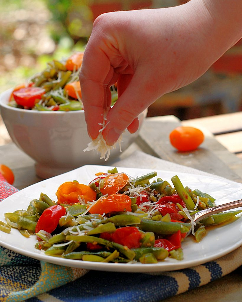 Italian Green Bean salad being topped with Parmesan cheese.