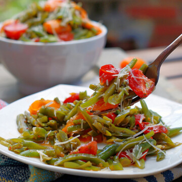 A forkful of Italian Green Bean Salad on a plate.
