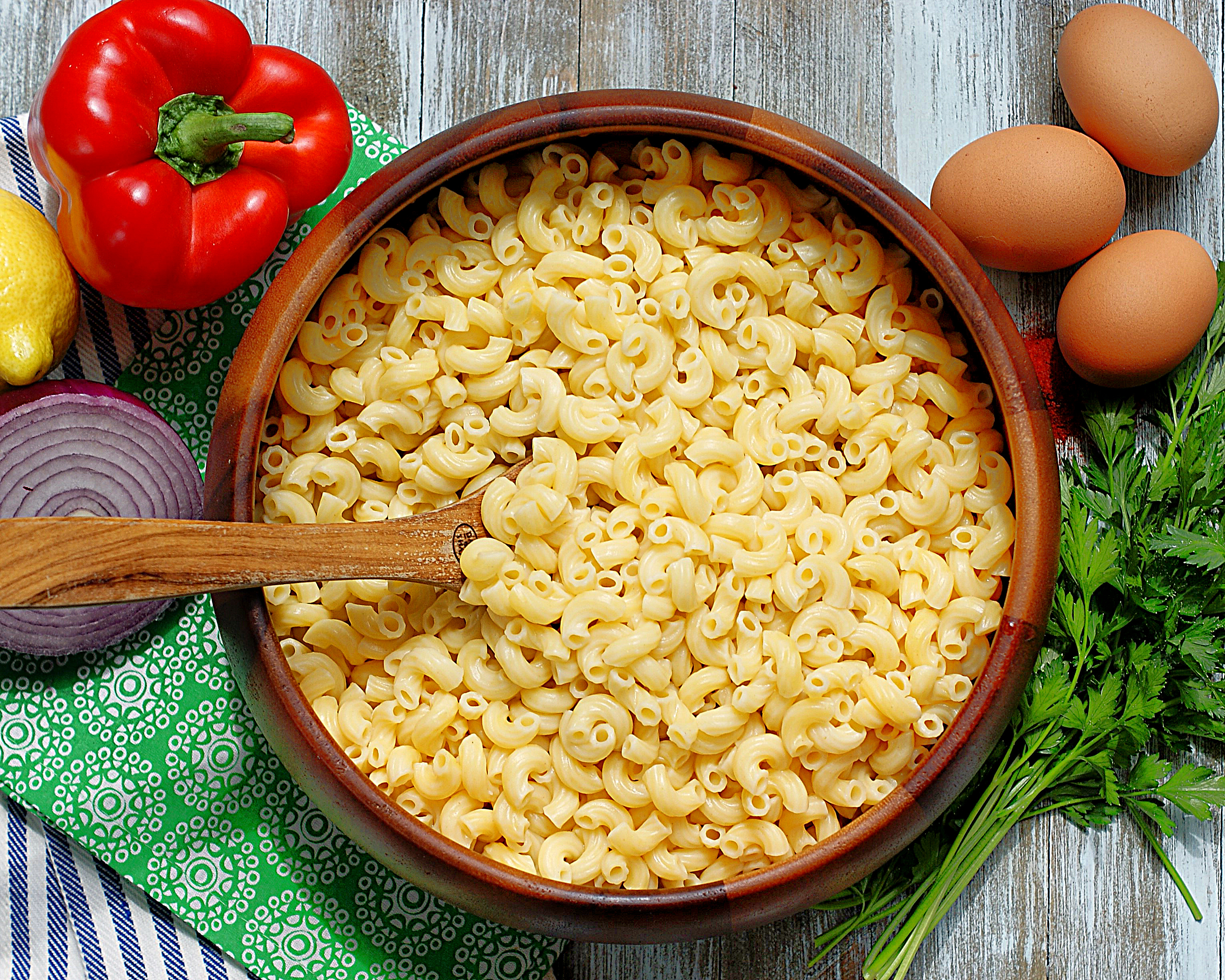A bowl of cooked elbow macaroni and ingredients for macaroni salad