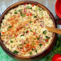 An aerial view of Southern Macaroni Salad bursting with red bell pepper, celery, red onion, sweet pickles and eggs.