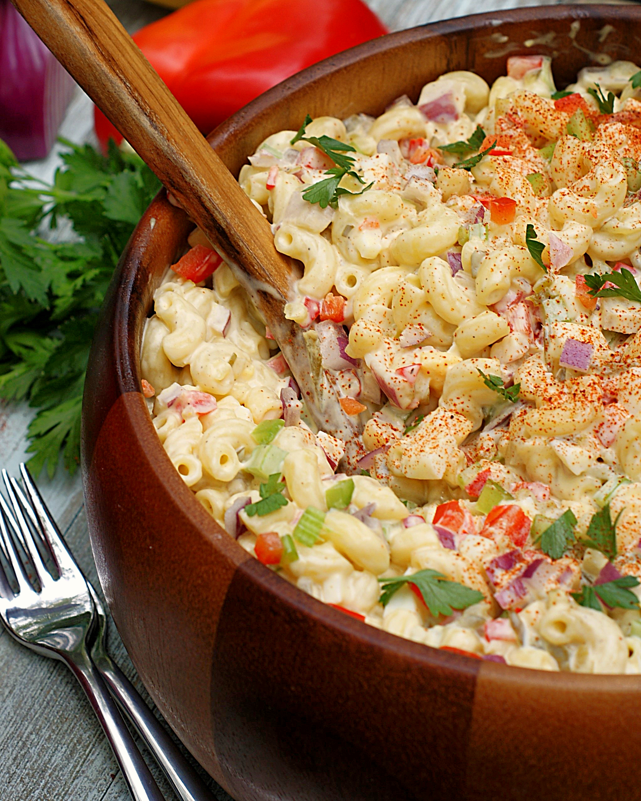 A bowl of southern macaroni salad loaded with red onion, red bell pepper, celery, boiled eggs and elbow macaroni.