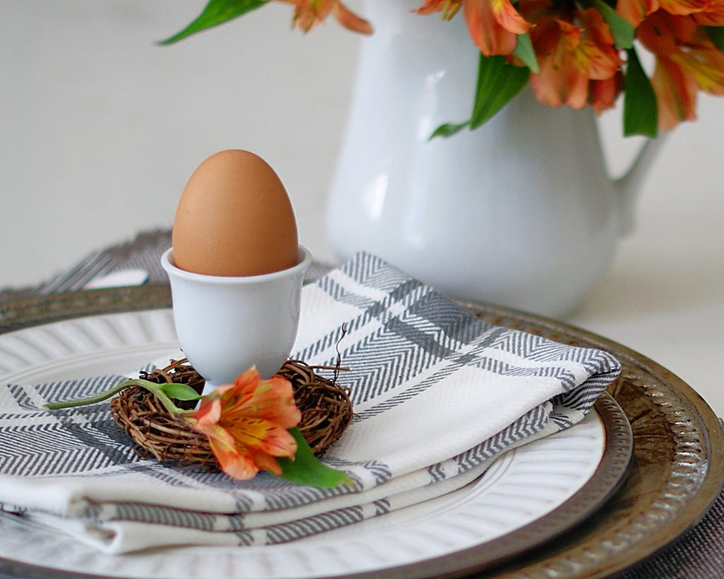 A brown egg in an egg cup on a white and bronze place setting with orange/peach colored flowers in a white vase.